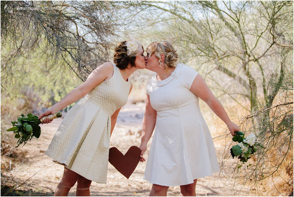 two brides kissing in desert with diy heart between them