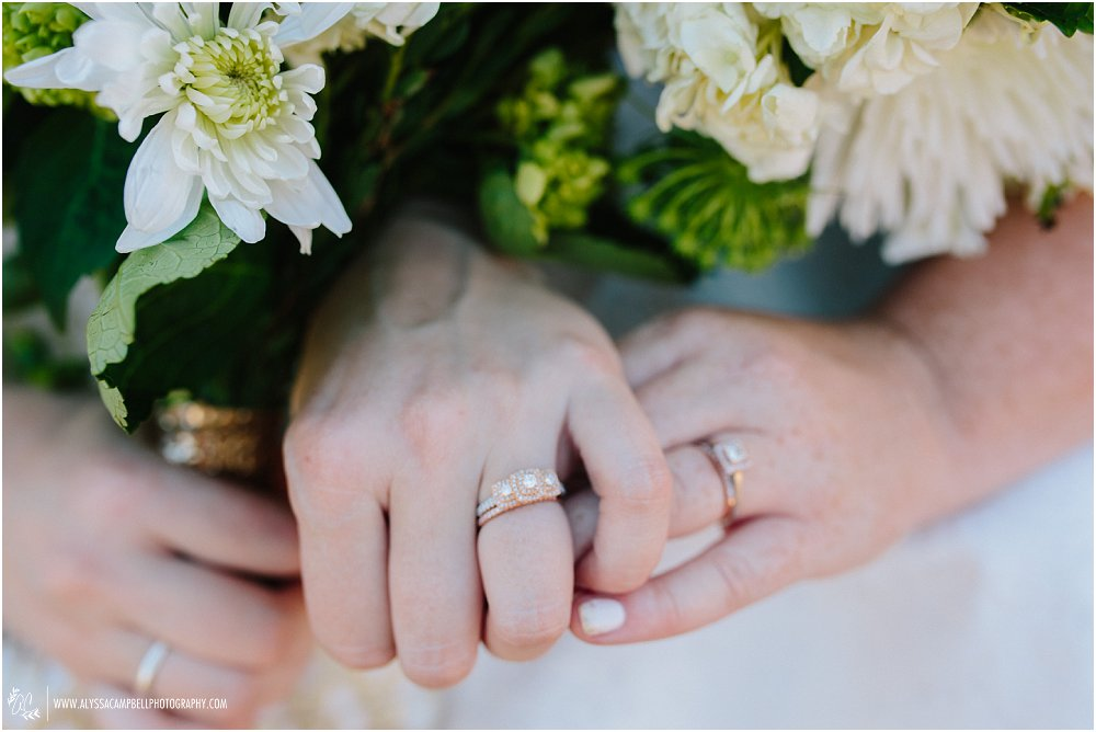 two brides holding bouquets with rings