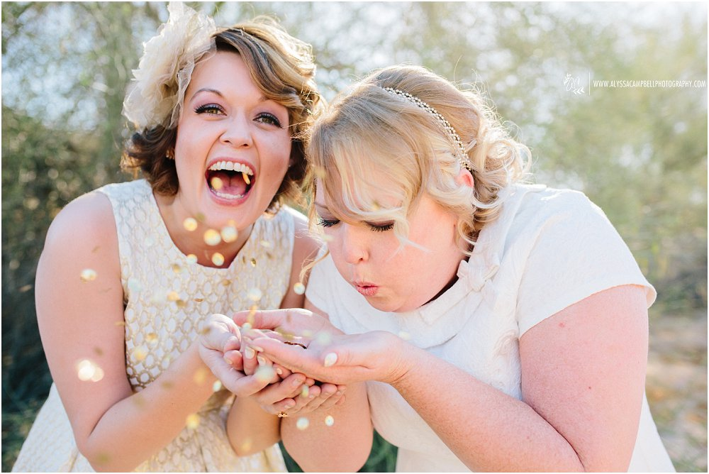 two brides blowing glitter laughing in Arizona desert