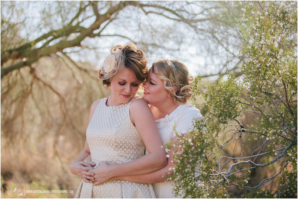 two lesbian brides in white & gold short dresses smiling in AZ desert