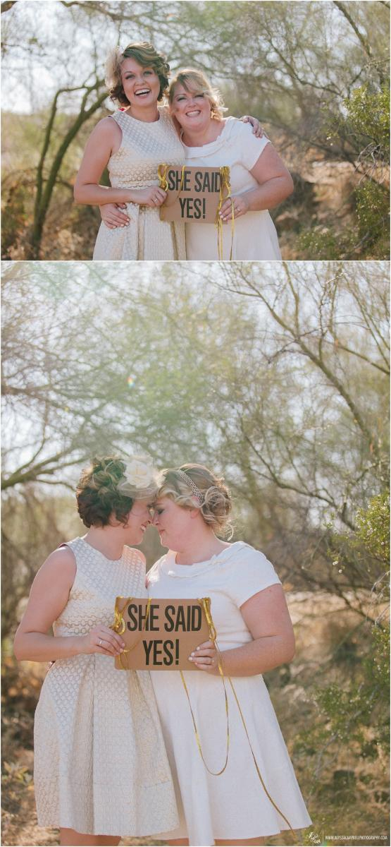 lesbian brides in gold & white short dresses holding she said yes signs laughing