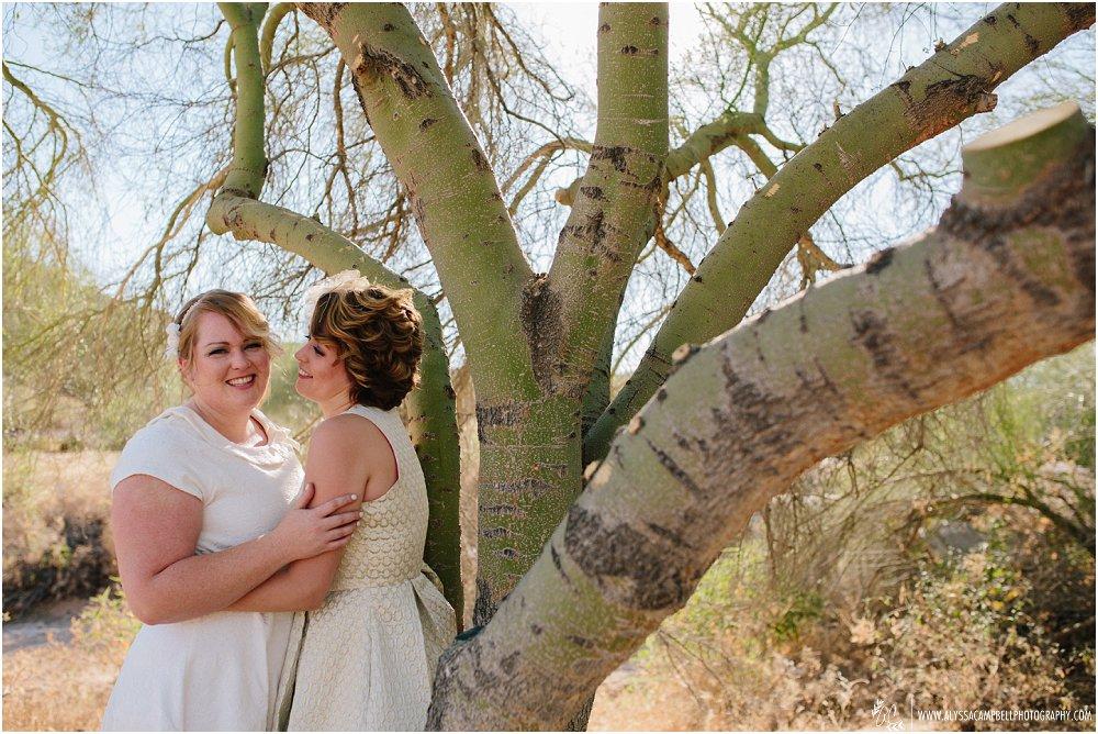 two lesbian brides in gold & white short dresses in AZ desert by Arizona same sex wedding photographers
