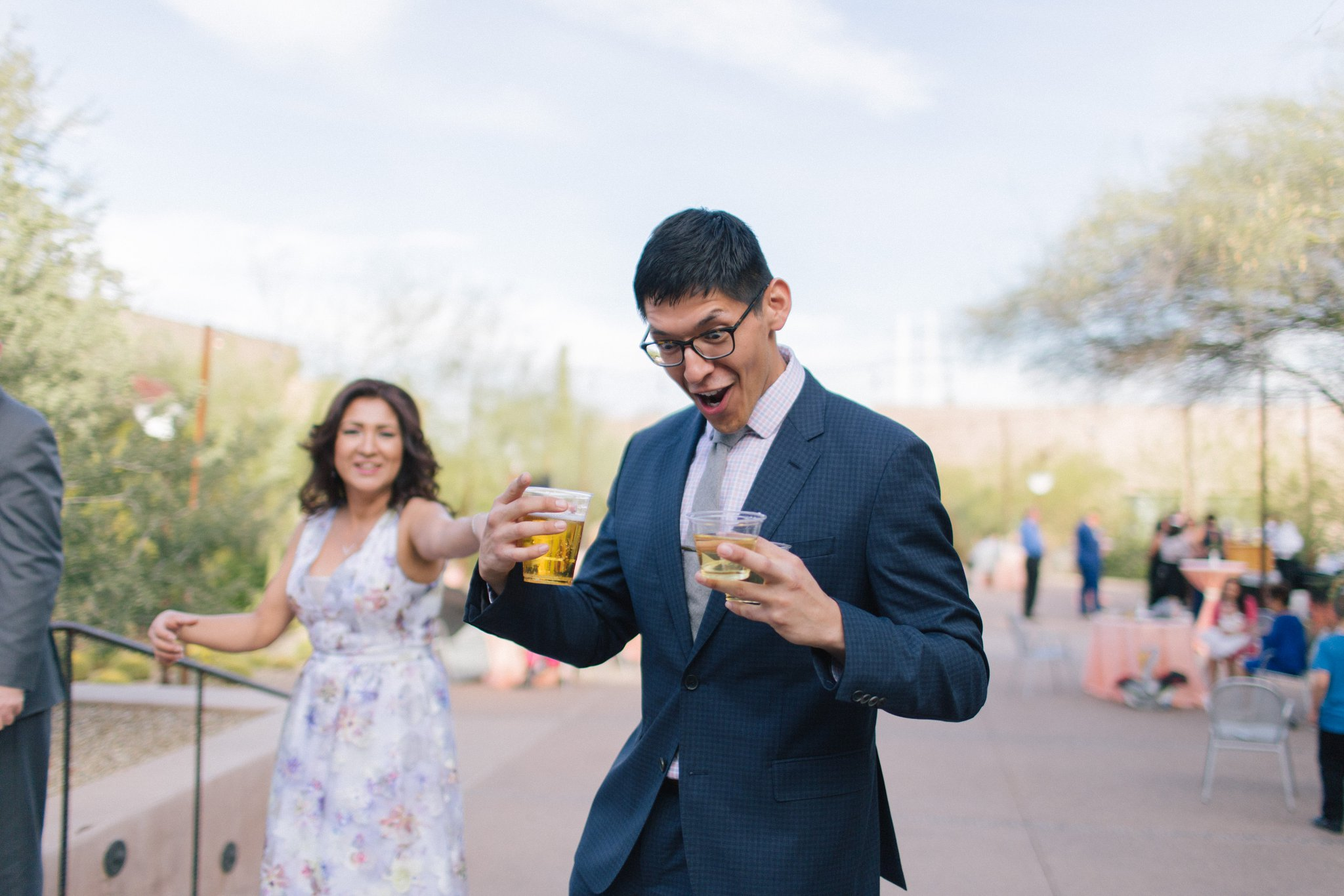 guy holding beer excited Phoenix candid wedding photographer