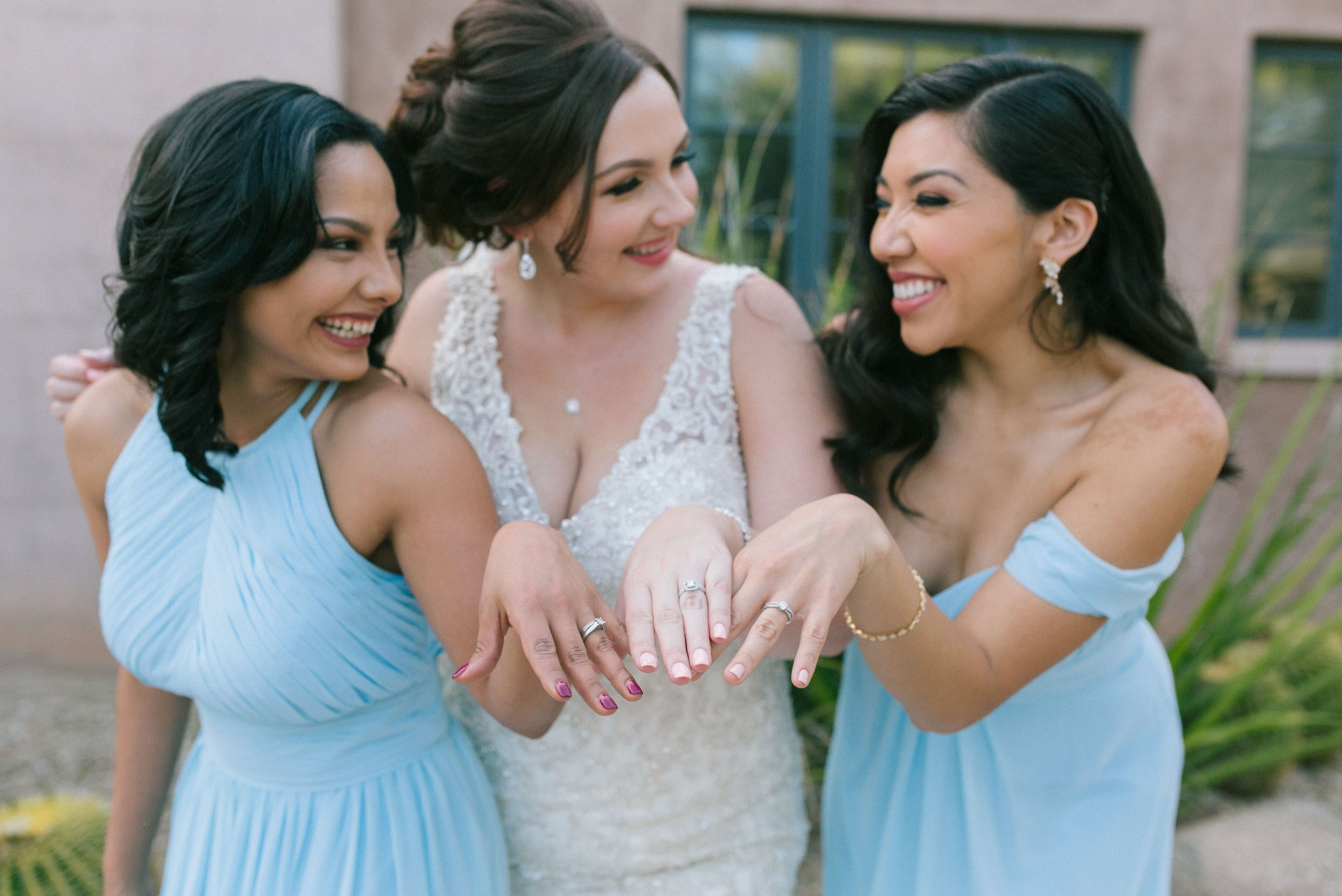 bridesmaids and bride with wedding rings laughing