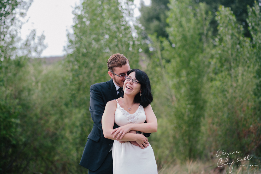 bride and groom laughing in field in Prescott