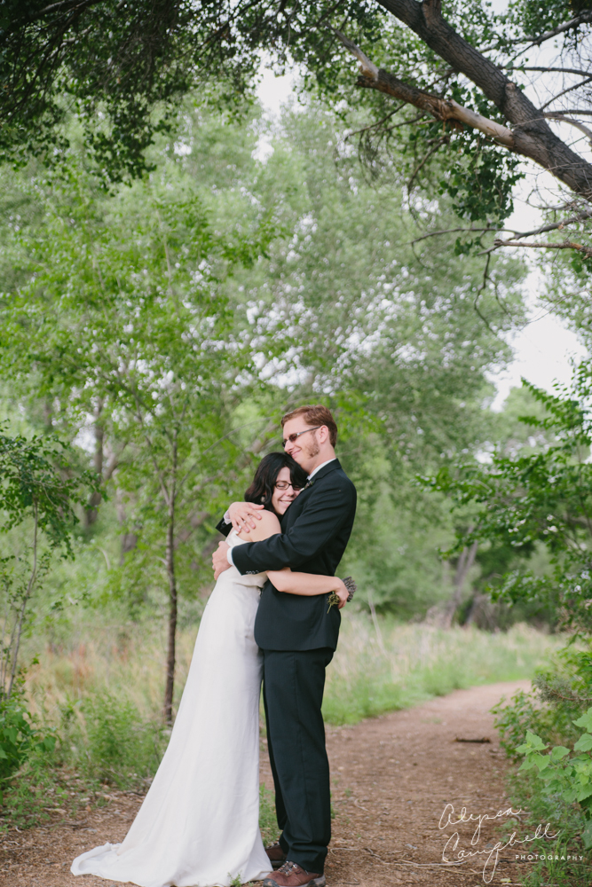 bride and groom with glasses hugging in riparian preserve Prescott