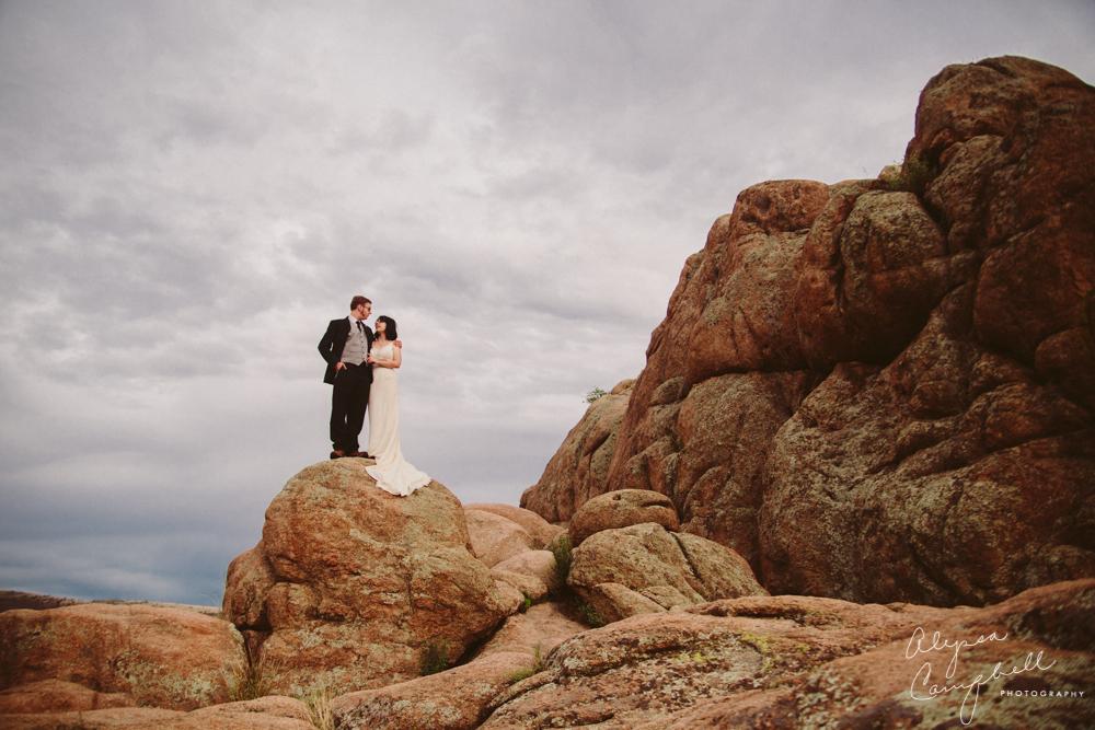 bride and groom on top of rocks at Watson Lake