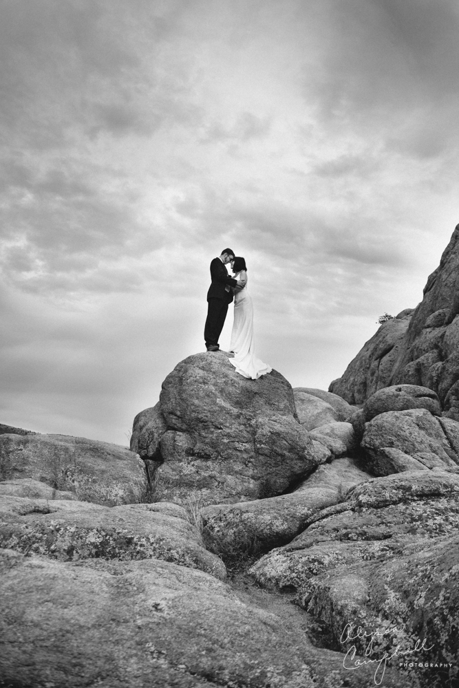 epic black and white photo of bride and groom on rocks in Watson Lake Prescott