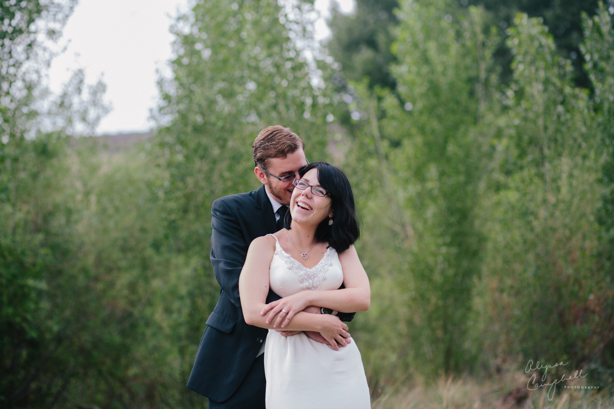bride and groom laughing together in field Northern Arizona