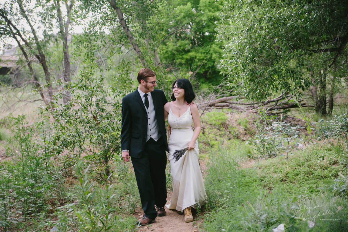 bride & groom hiking in green Arizona forest after wedding