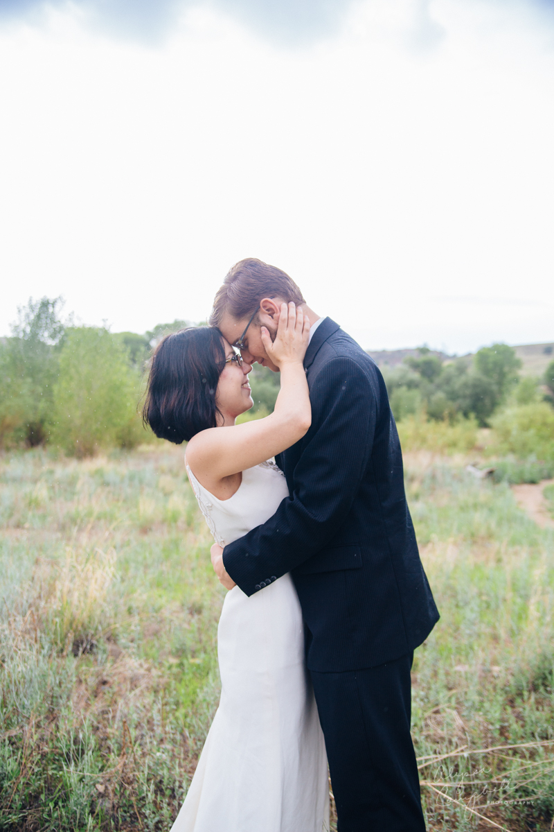 bride and groom with foreheads together laughing in field