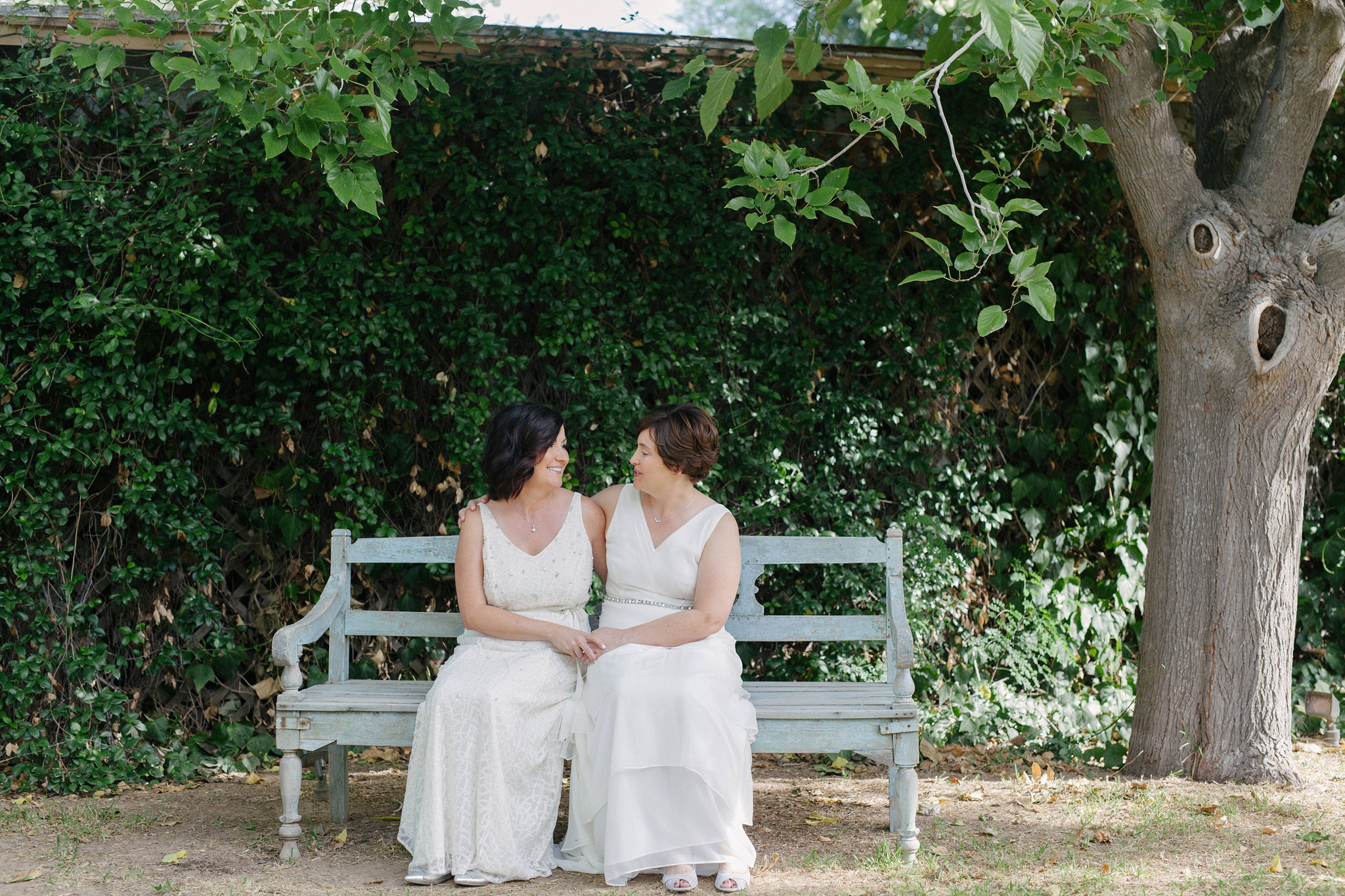 natural candid portraits two brides in white dresses at gay wedding Farm at South Mountain