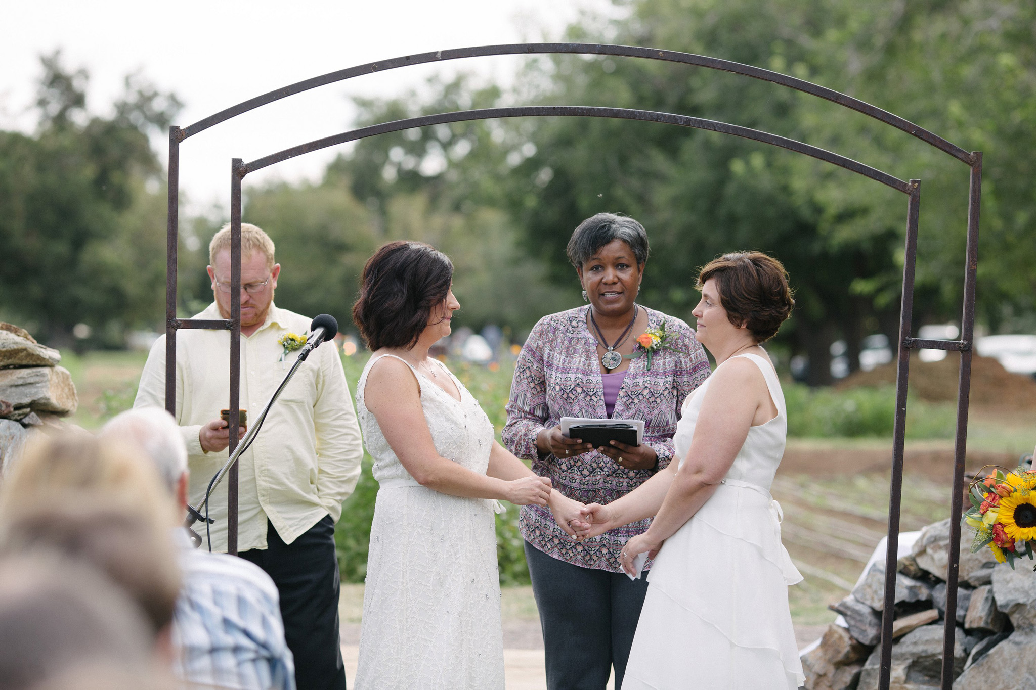 lesbian wedding ceremony two brides in white dresses at Farm at South Mountain