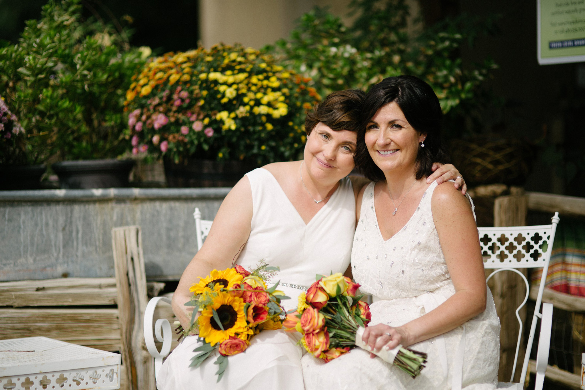 two older brides in white dresses at Farm at South Mountain gay wedding