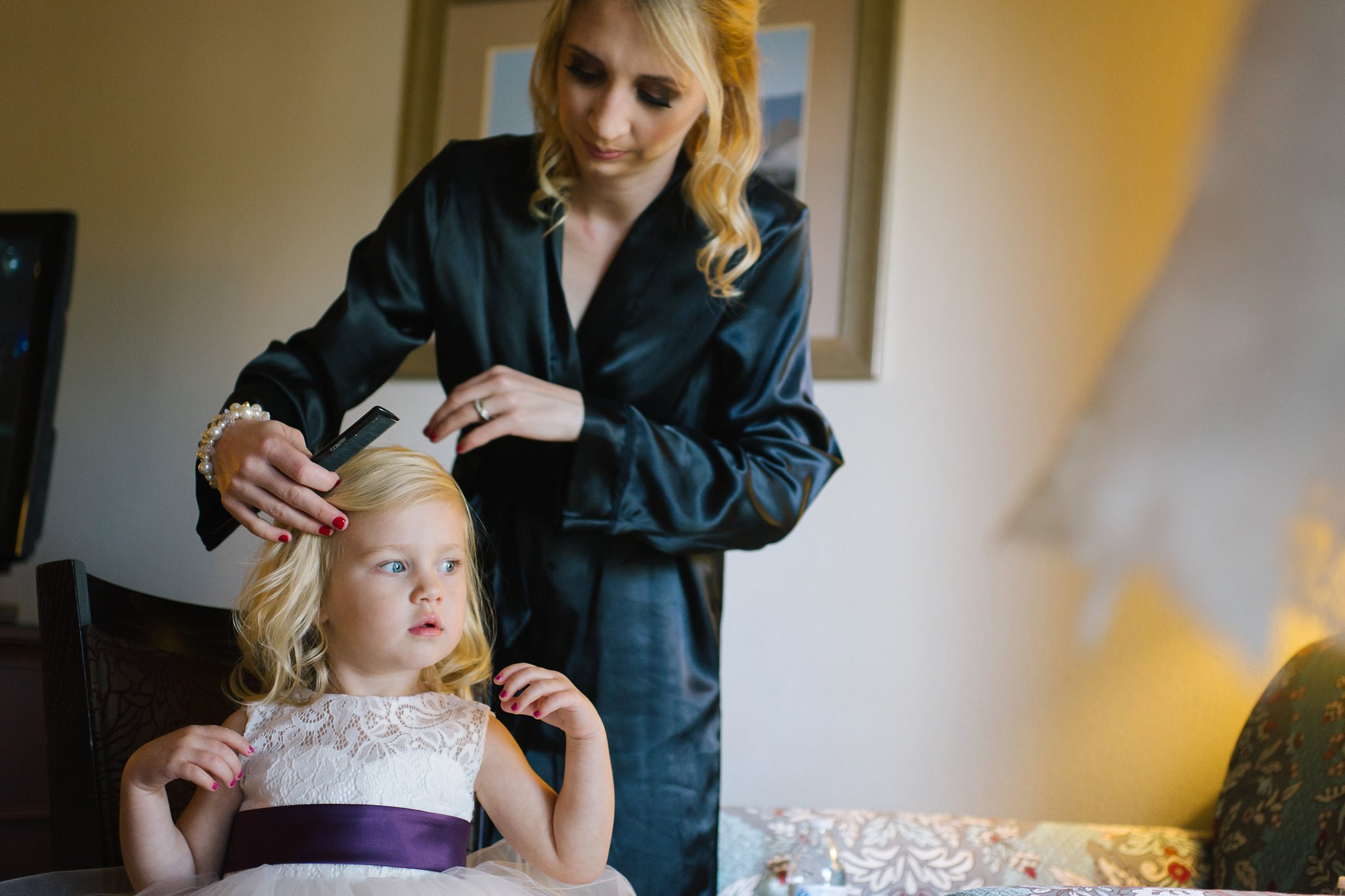 mother getting flowergirl ready for wedding