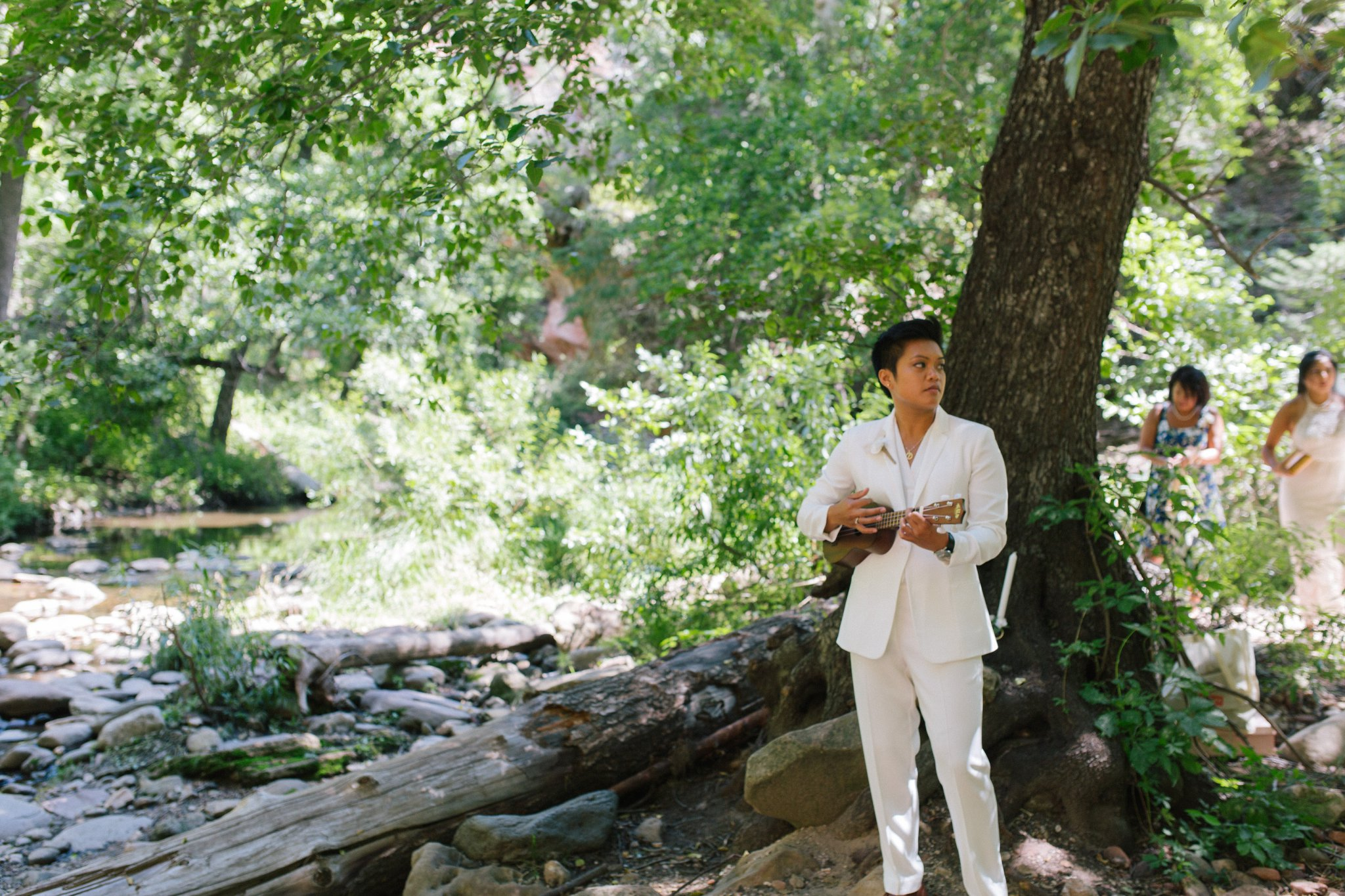 bride in pantsuit playing ukelele at West Fork Sedona elopement