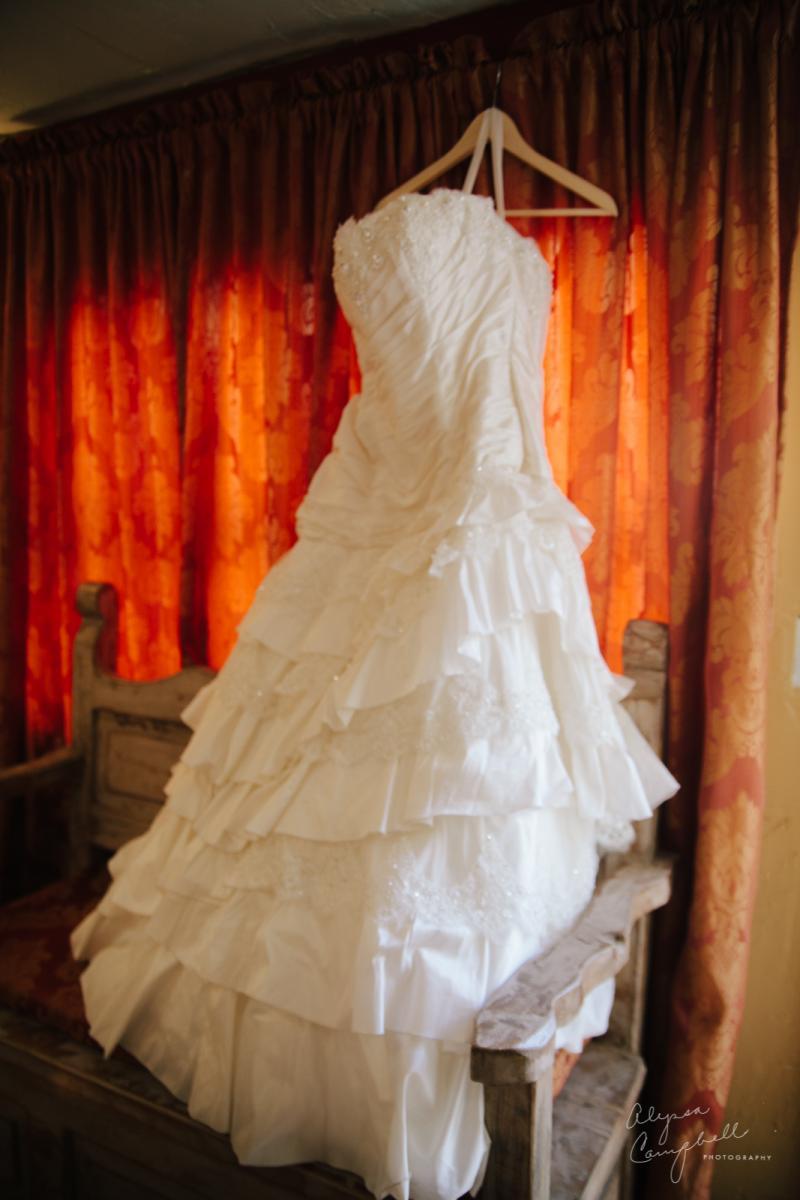 beautiful plus sized wedding dress hanging in window with ruffled skirt