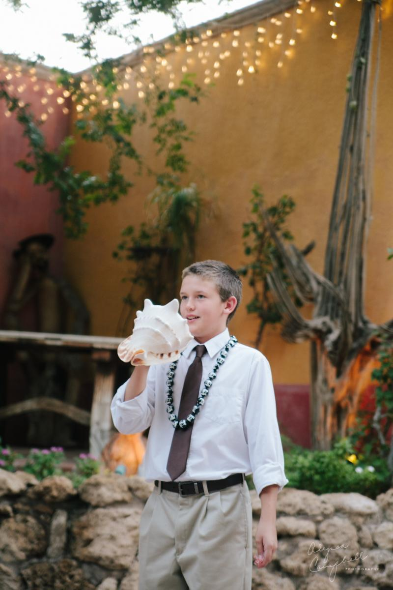 little kid blowing conch shell at beginning of traditional Hawaiian elopement ceremony