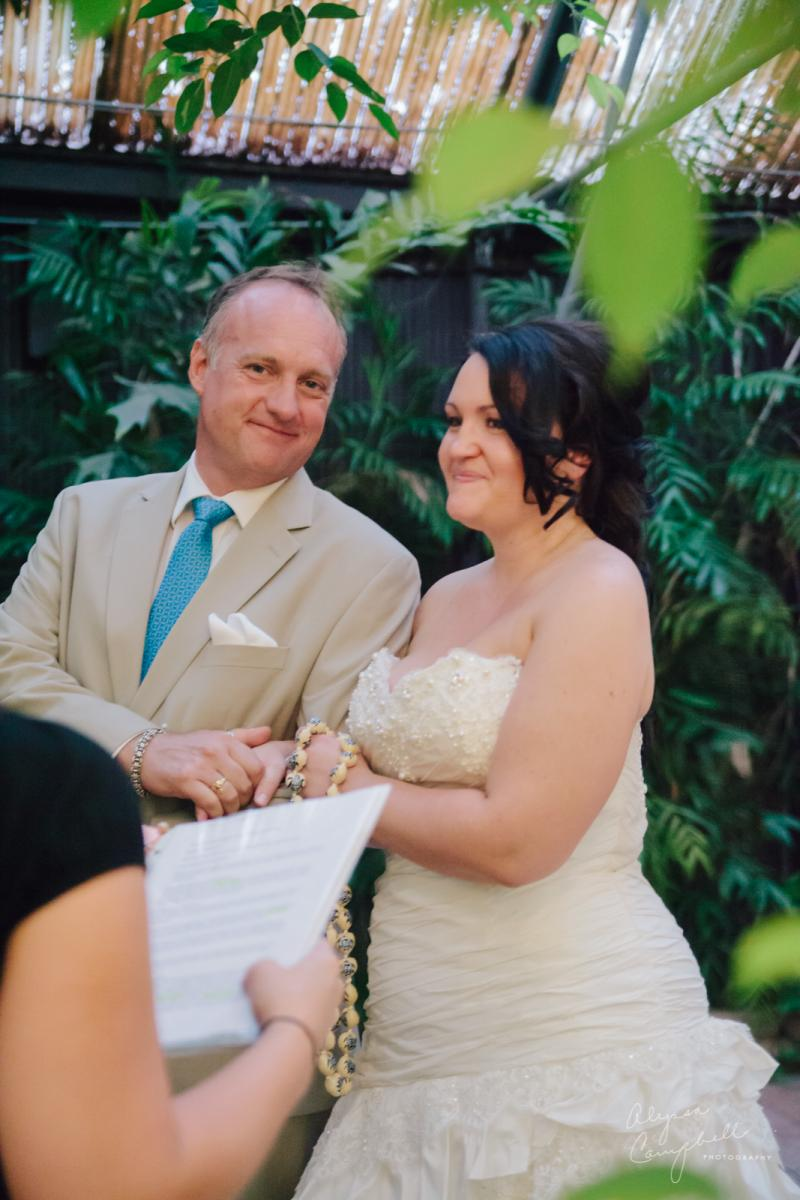 bride and groom looking at officiant at elopement at Boojum Tree greenhouse