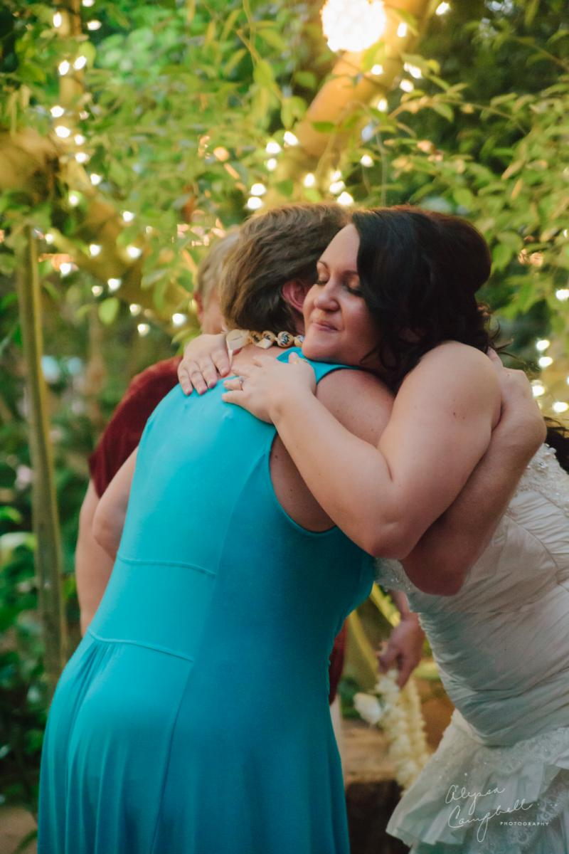 mother in law hugging bride and welcoming into family
