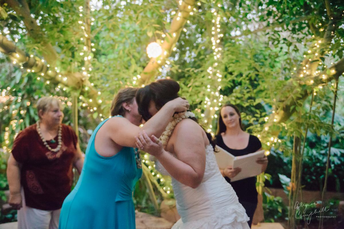 bride being welcomed into family by mother in law placing lei on neck Hawaiian tradition