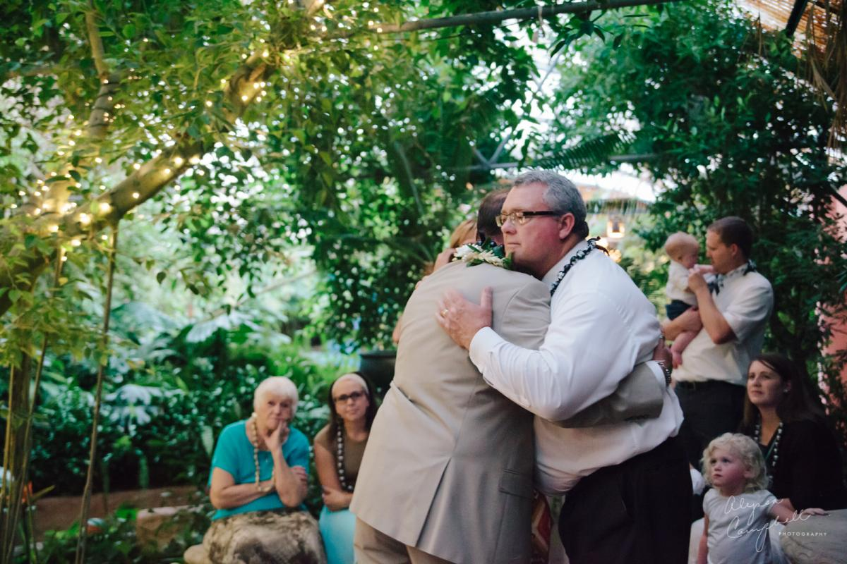 father in law hugging groom welcoming into family at wedding ceremony