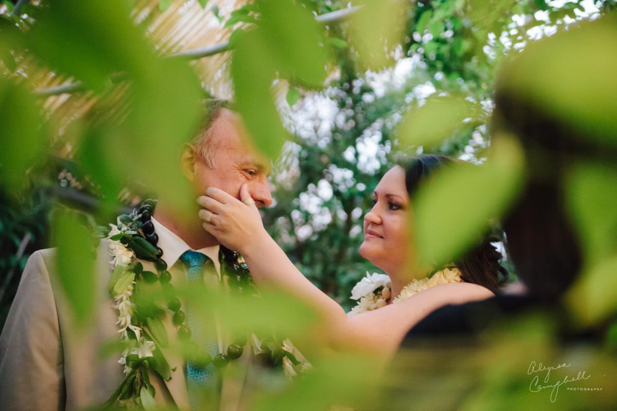 beautiful photo of bride wiping tear away from groom's eye at ceremony at Boojum Tree greenhouse