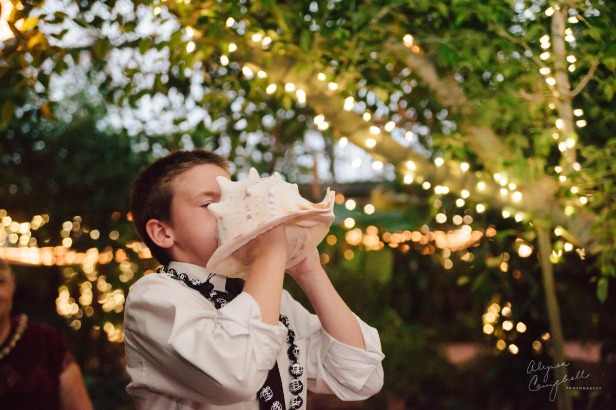 little kid blowing conch shell at end of traditional Hawaiian ceremony