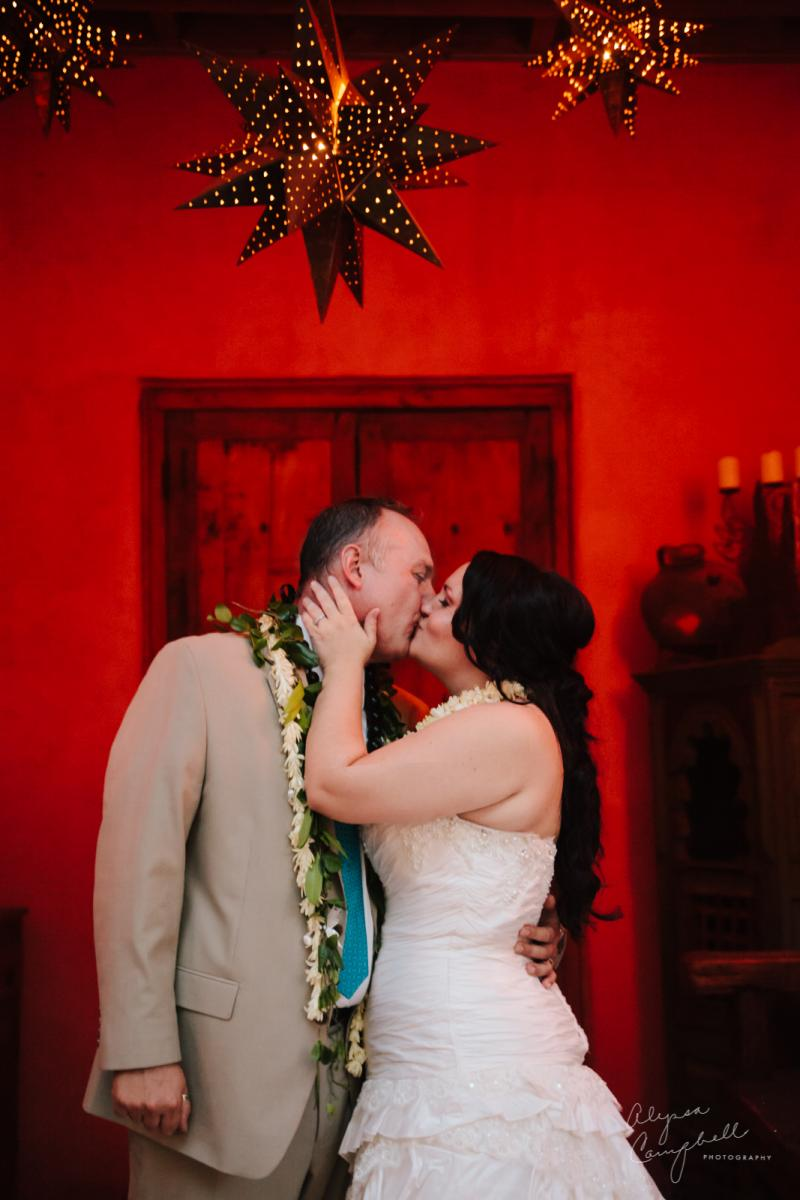 bride and groom in front of red wall with star lanterns at Boojum Tree Hidden Gardens Hawaiian elopement