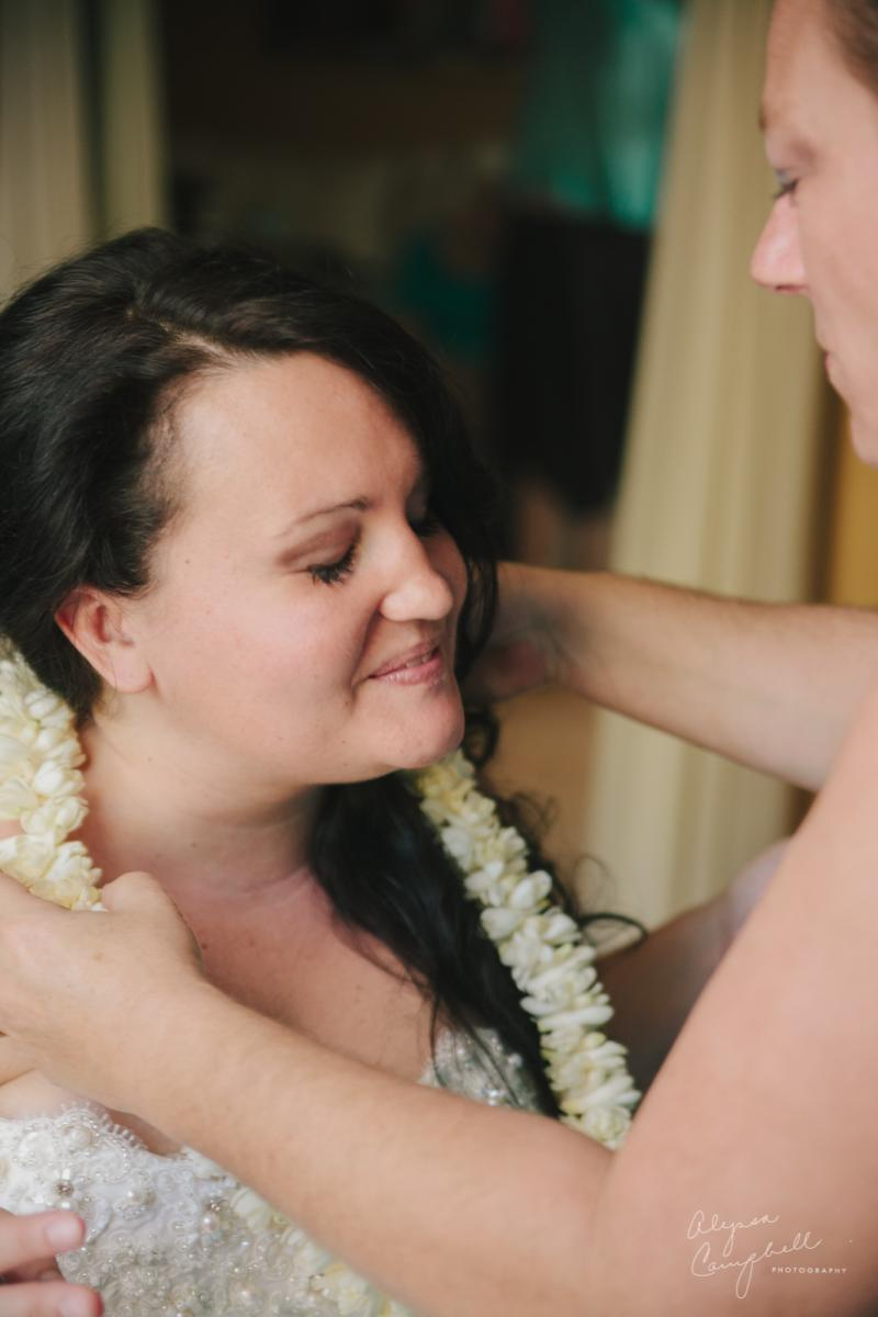 mother putting on daughter's wedding lei from Hawaii