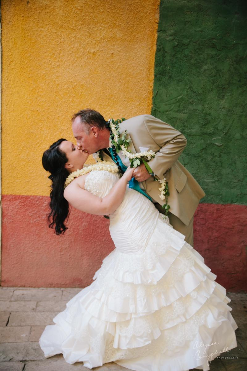colorful romantic photo of groom dipping bride and kissing at Boojum Tree with Hawaiian leis