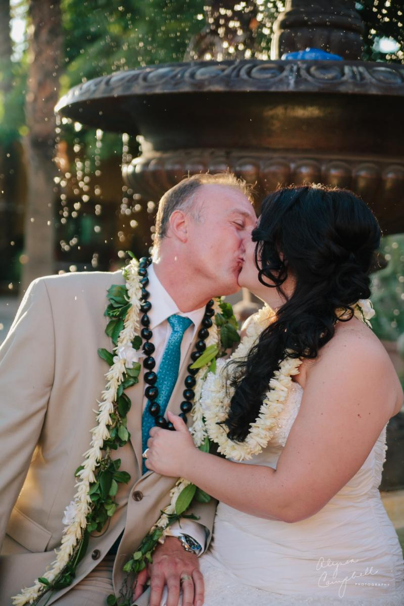 Hawaiian elopement at Boojum Tree couple kissing in front of fountain