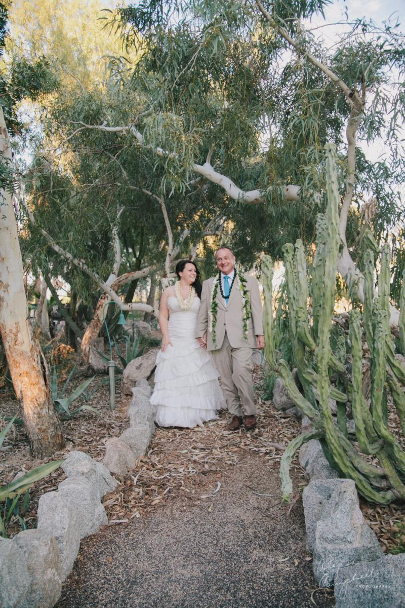 bride and groom walking down pathway with desert and eucalyptus trees at Boojum Tree