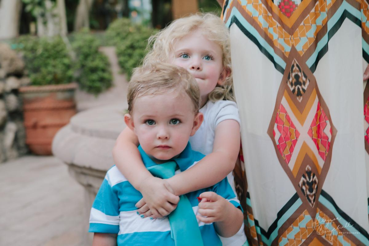 candid photo cute blonde brother and sister at wedding hugging