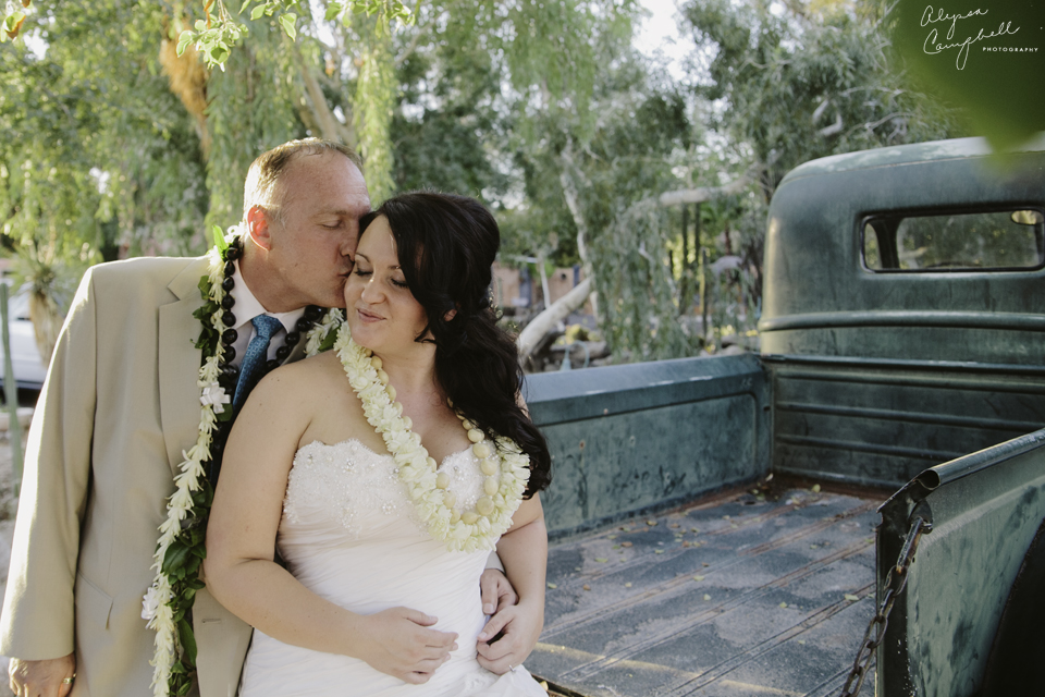 bride and groom portrait kissing and cuddling on old teal truck at Boojum Tree wedding venue