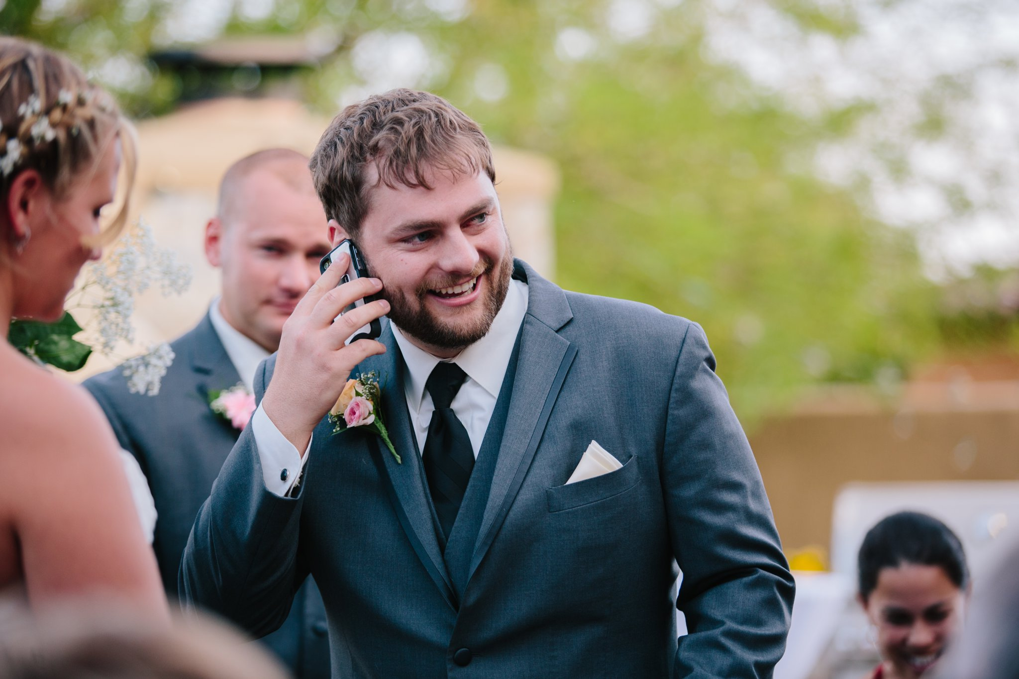 groom calling grandparents during ceremony on cell phone