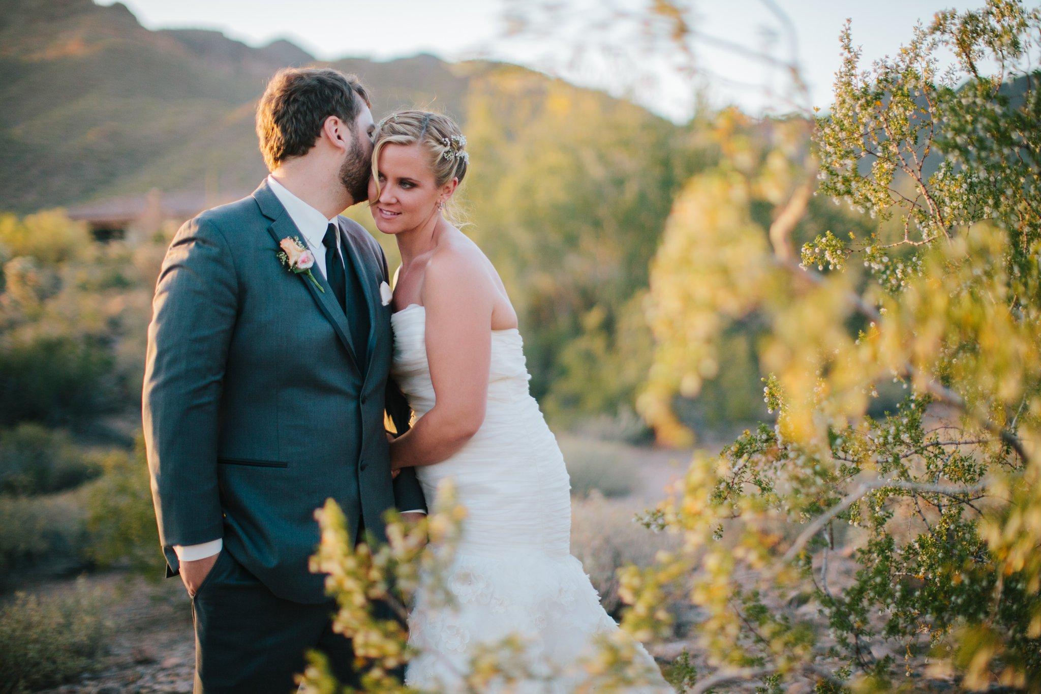 groom whispering in bride's ear in desert at sunset in AZ