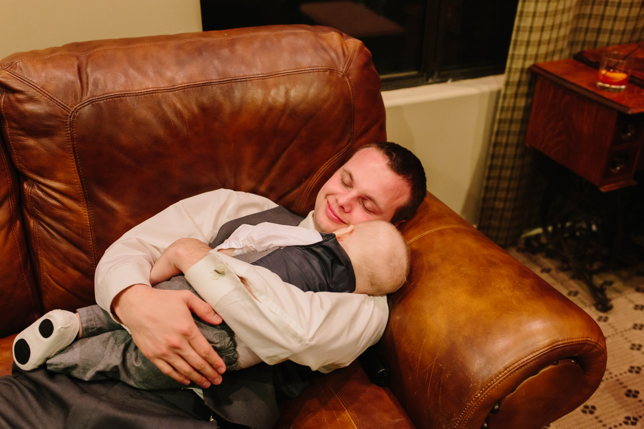 dad and son sleeping after wedding on couch