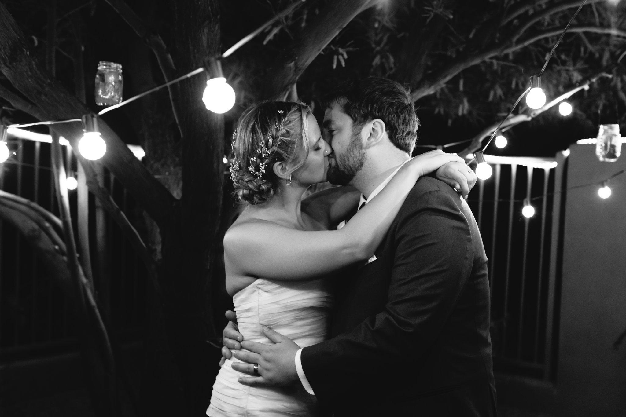 bride & groom kissing at night under string lights in AZ