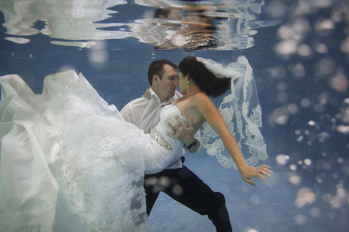 bride and groom underwater with wedding clothes Arizona underwater trash the dress photographer