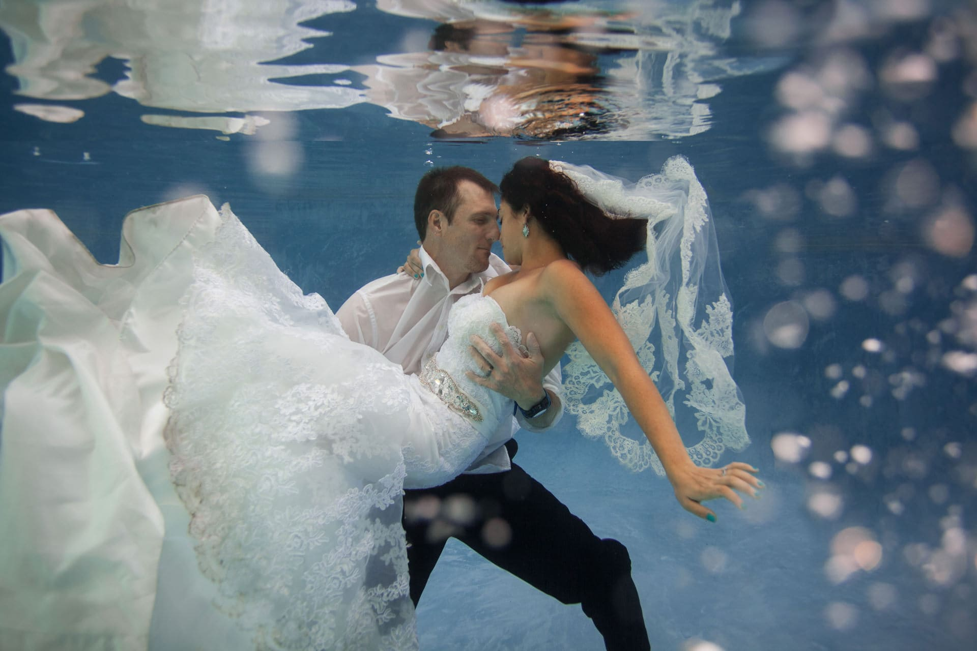 bride and groom underwater with wedding clothes