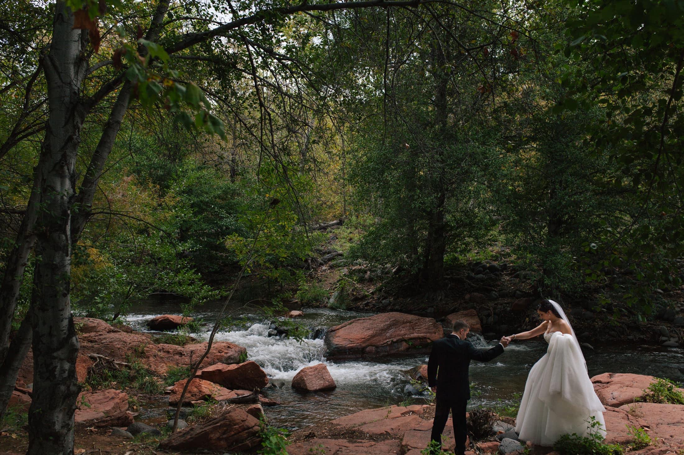 bride and groom walking along Oak Creek in Sedona