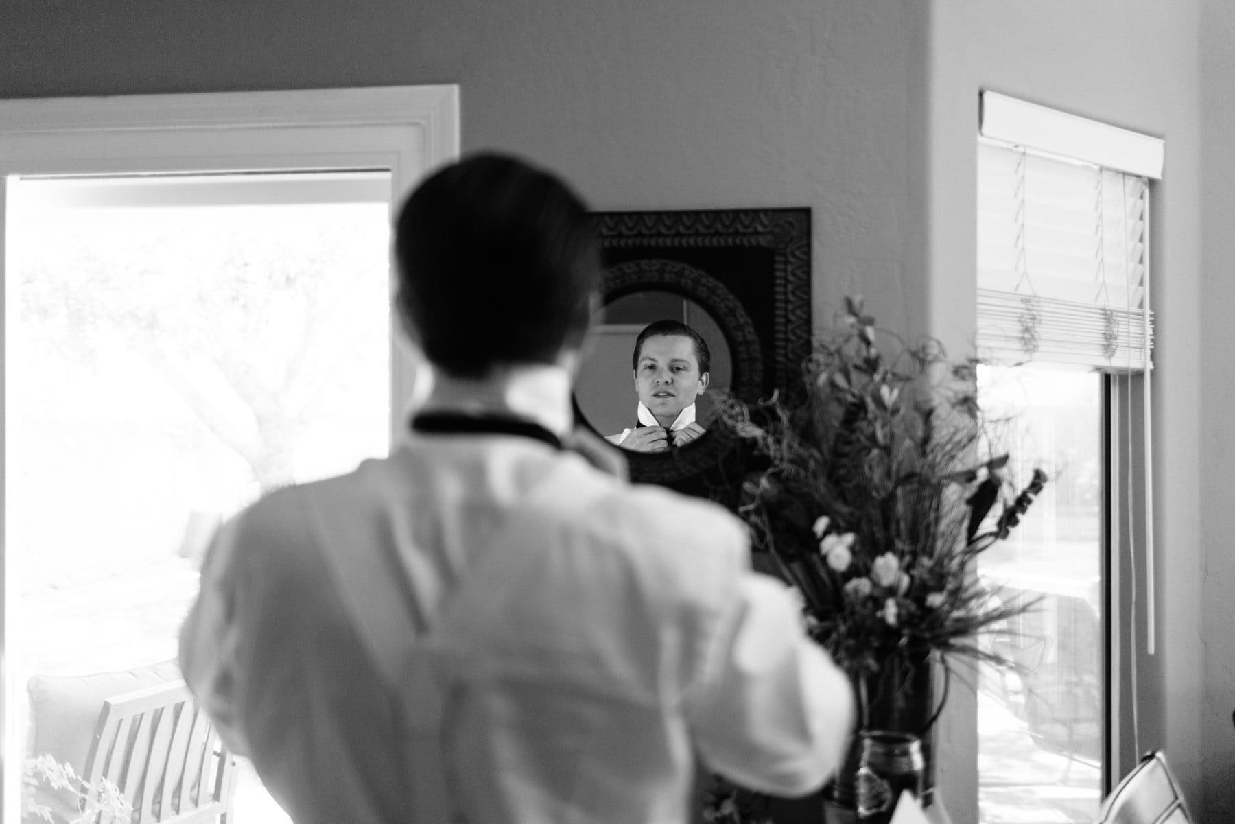 groom getting ready in Scottsdale, AZ home looking into mirror adjusting tie