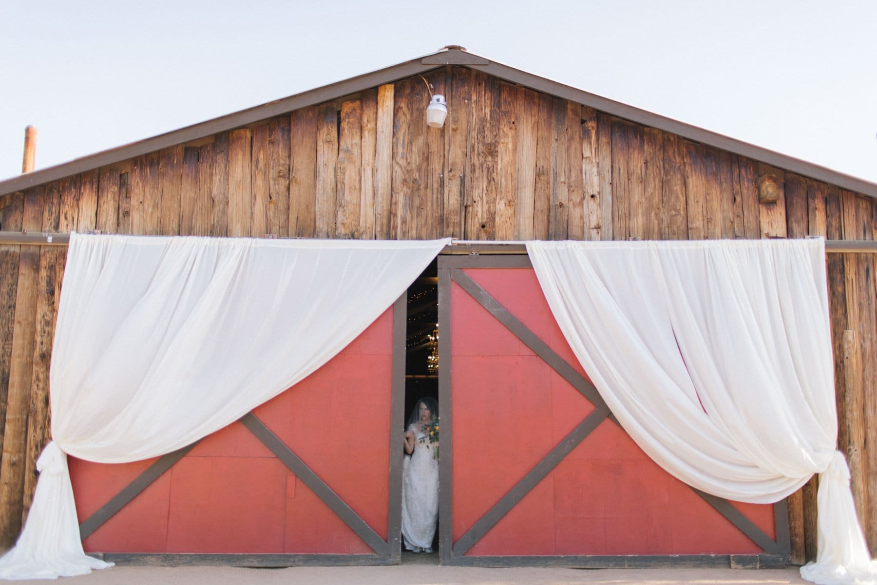 red barn doors bride walking to ceremony at Desert Foothills wedding venue