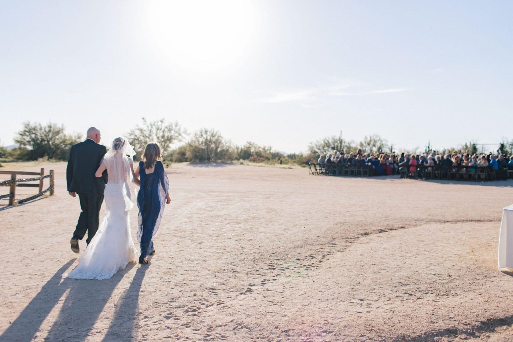 bride walking to desert ceremony at Desert Foothills barn wedding venue Scottsdale wedding photographer