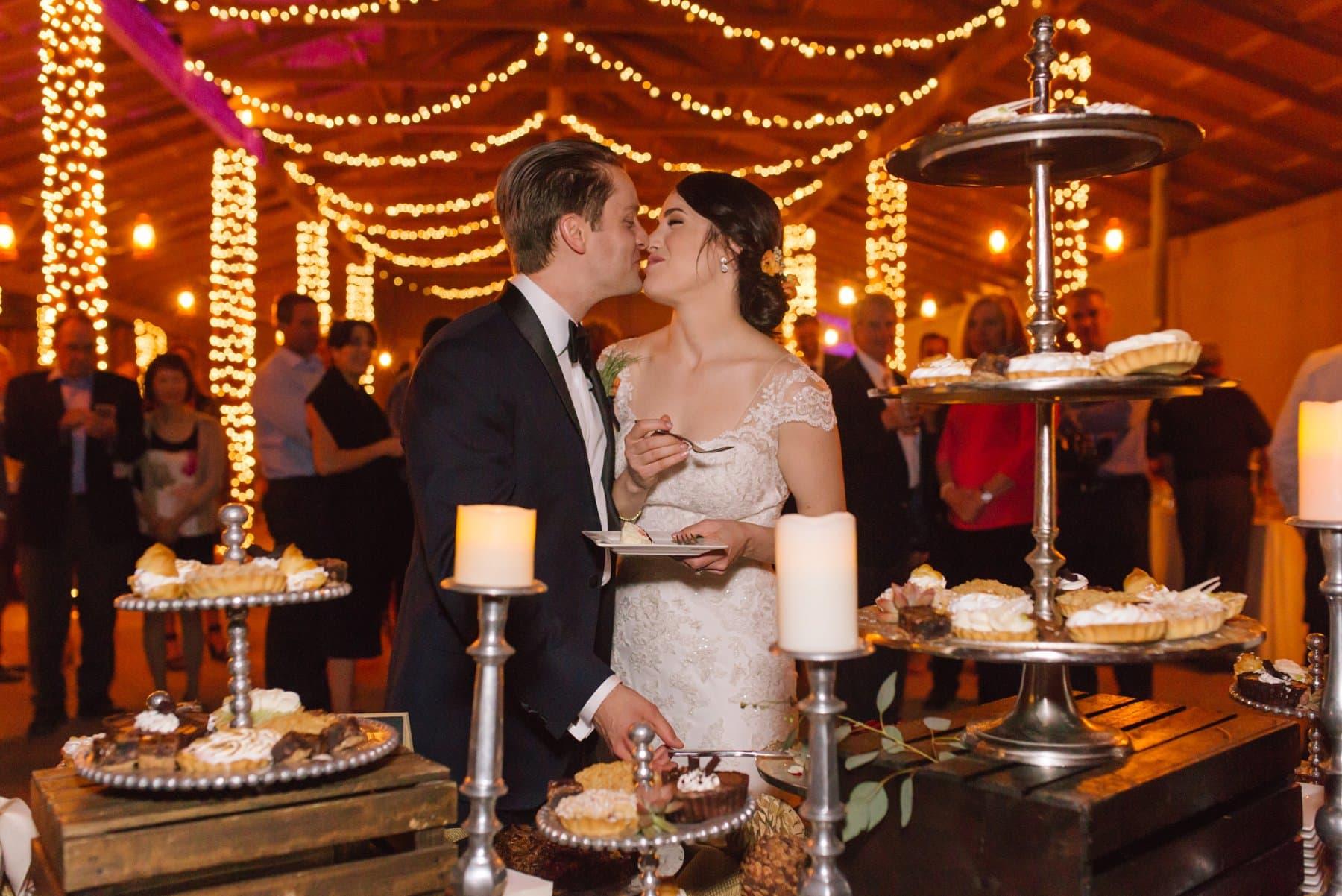 cutting wedding pie at elegant barn wedding Desert Foothills reception