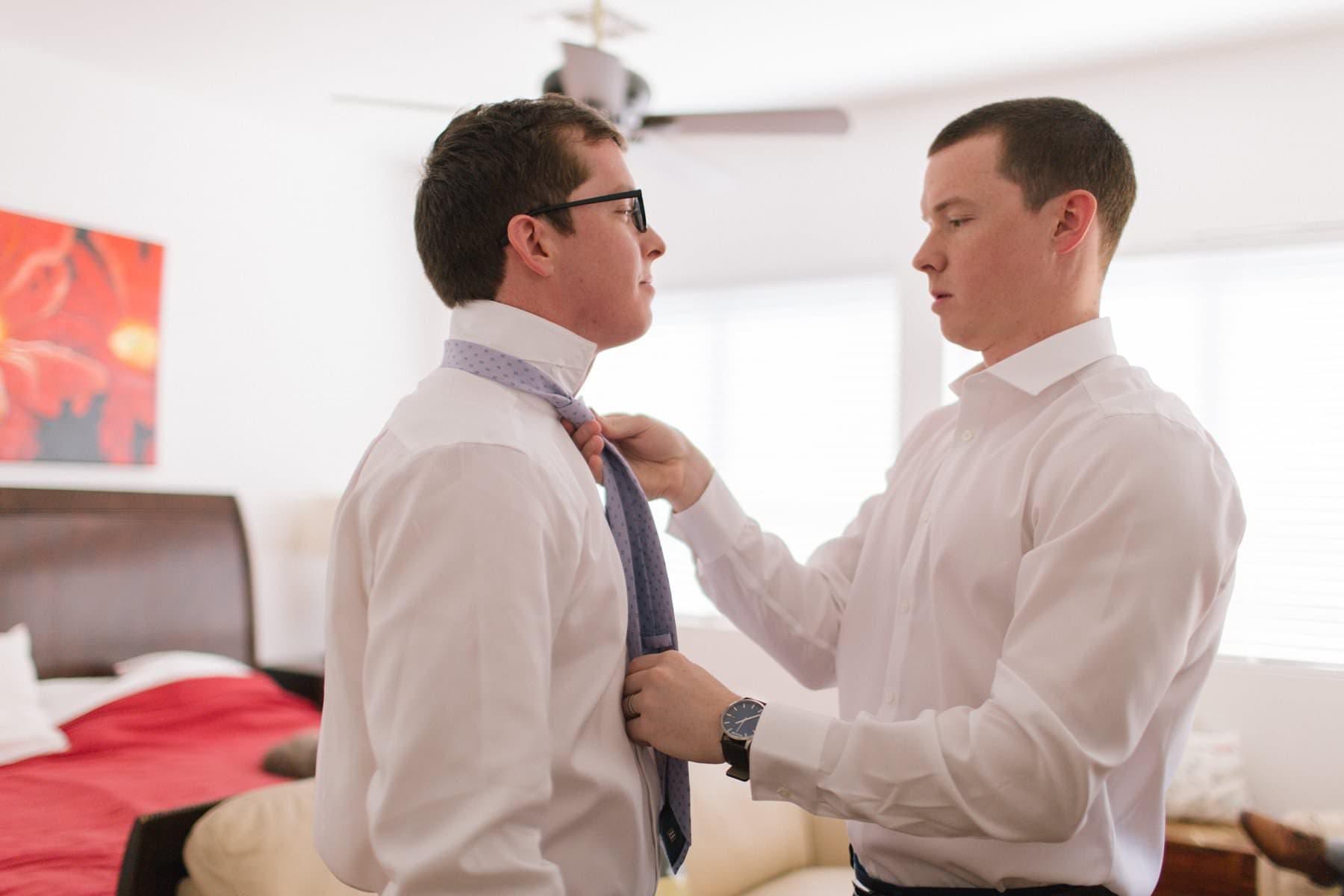brother helping groom get ready Mesa, AZ wedding photographer Alyssa Campbell