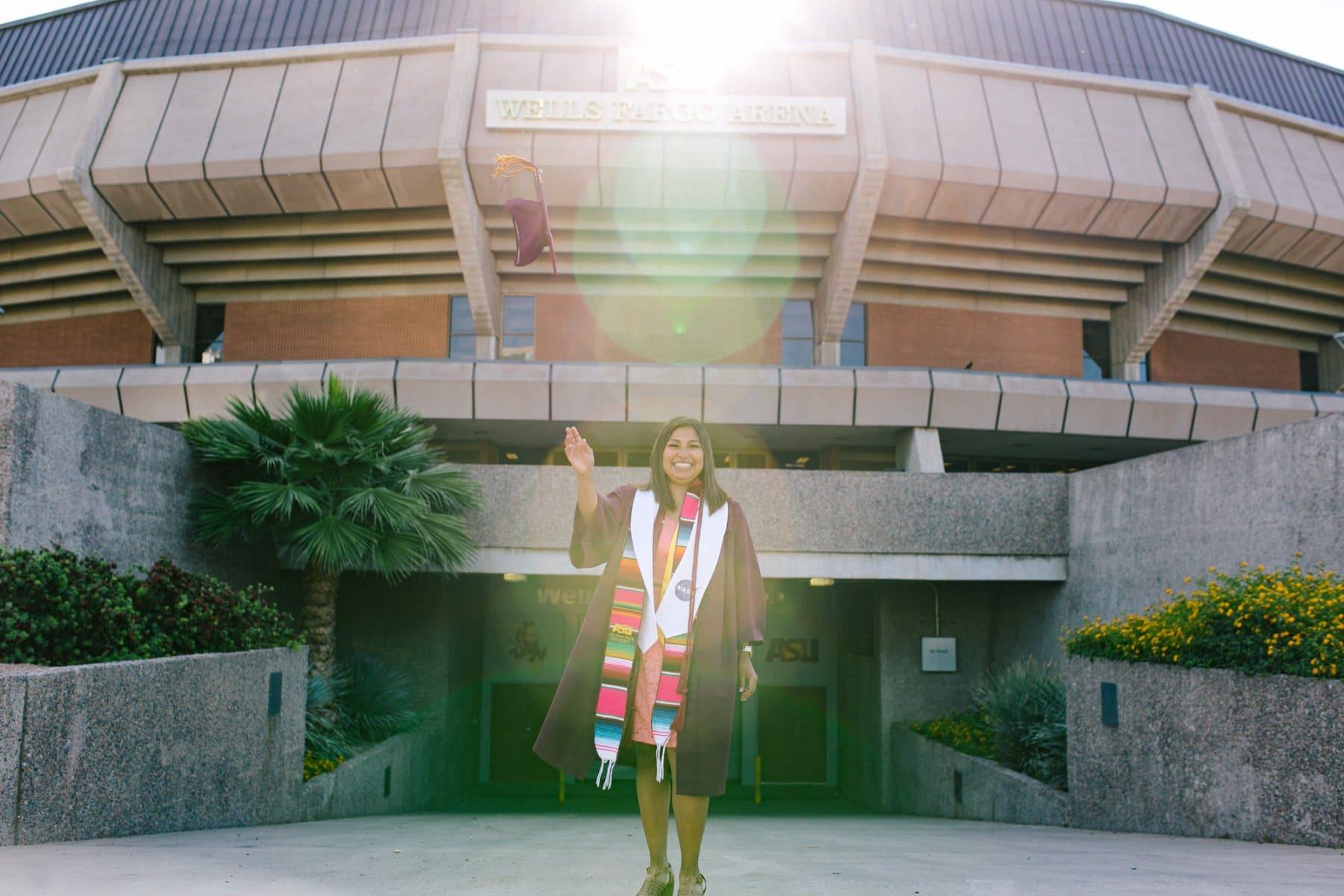 Arizona State University college grad tossing cap in front of Wells Fargo Arena