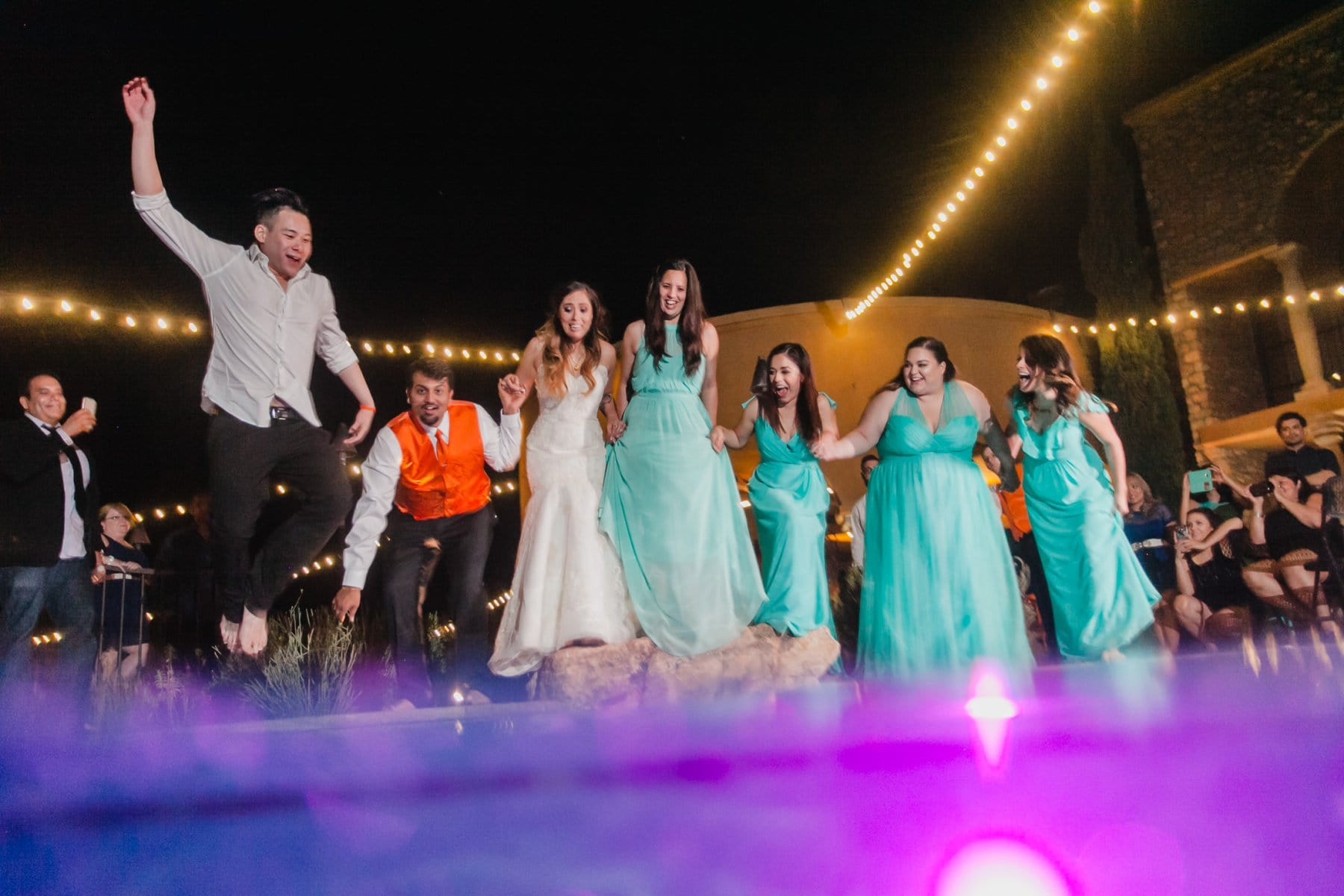 wedding party jumping into pool at reception