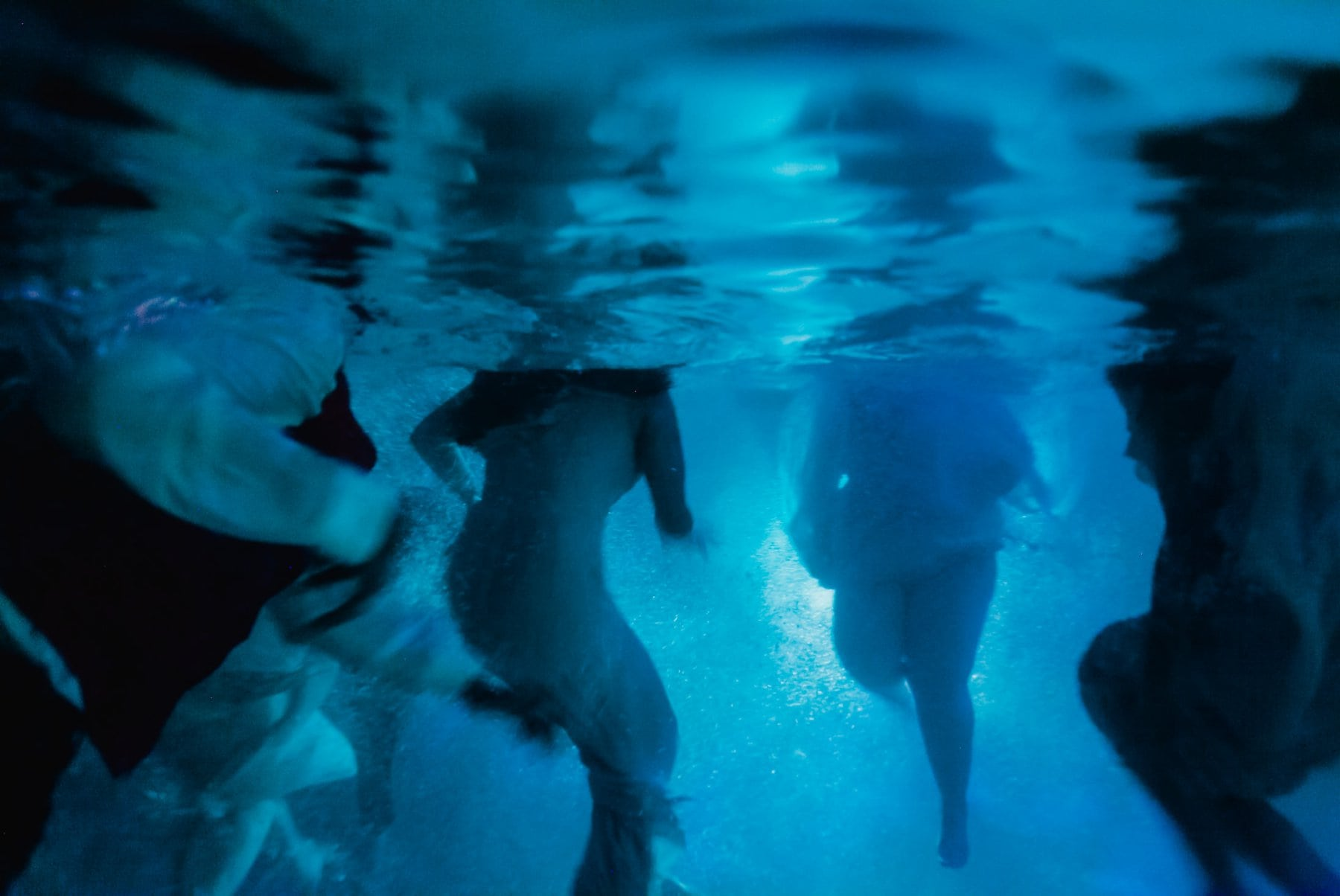 wedding party jumping into pool underwater